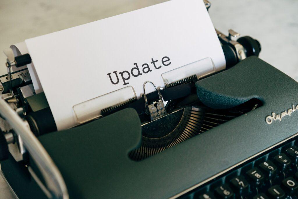 """Foto einer Schreibmaschine aus der ein Blatt mit der Überschrift """"Update"""" ragt."""