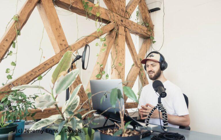 Mann sitzt in einem hellen Raum vor einem Laptop und nimmt einen Podcast auf.