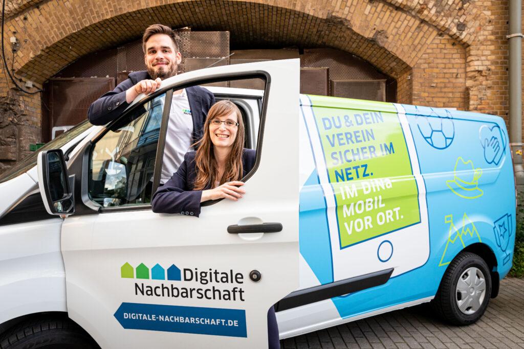 Petra und ihr Kolle schauen durch die offene Tür des geparkten Dina-Mobils mit grün-blauem Aufdruck