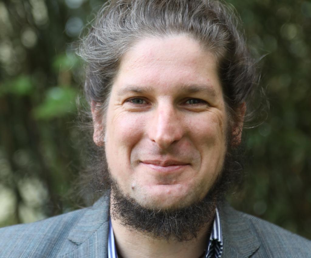 Portrait von Michael Mischke von WECHANGE, er trägt einen Bart und lange zum Knoten gebundene dunkle Hare und lacht in die Kamera.
