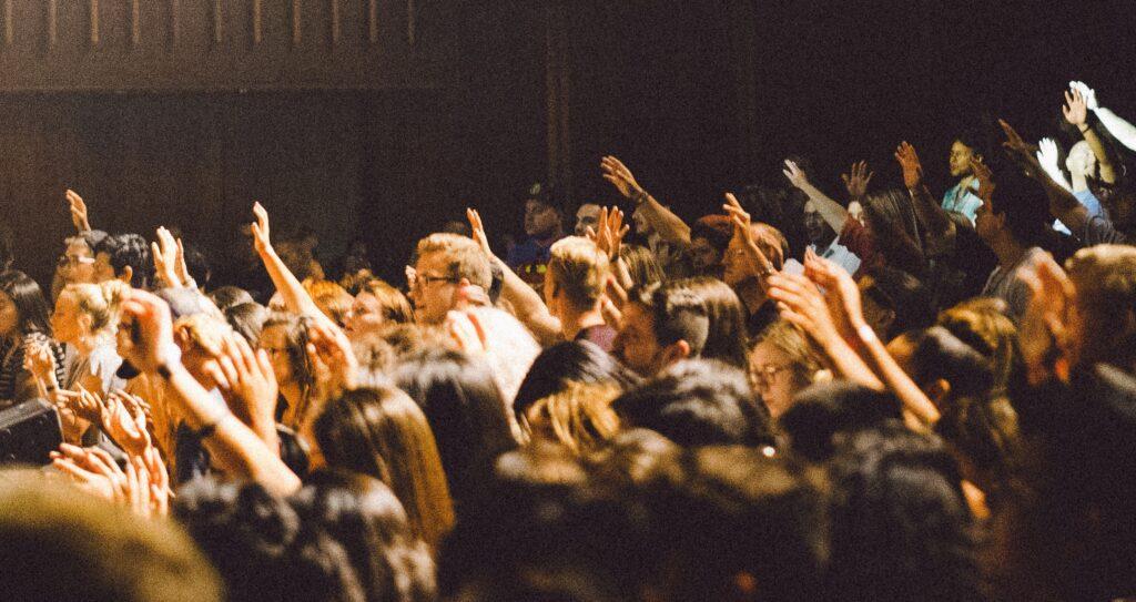 EIne Menschenmenge in einem Aufitorium Viele Hände sind als Meldung gereckt.
