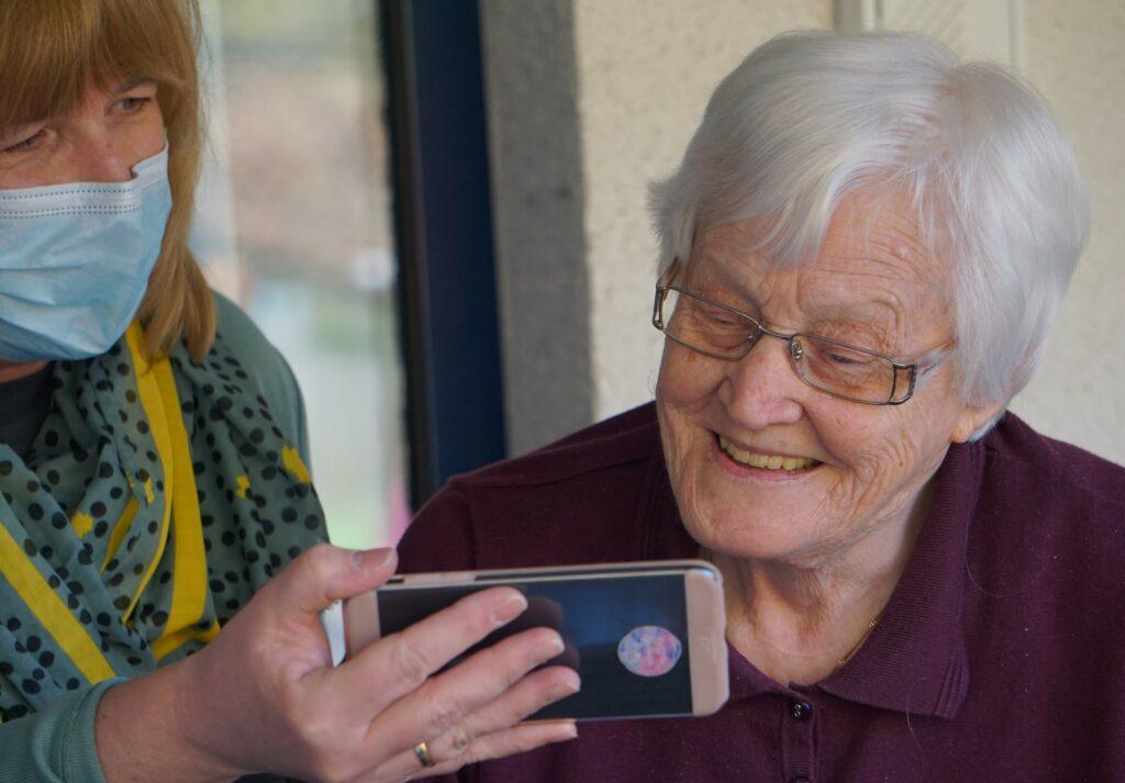 Pflege digital: Ehrenamtliche Pflegerin zeigt einer Seniorin ein Smartphone