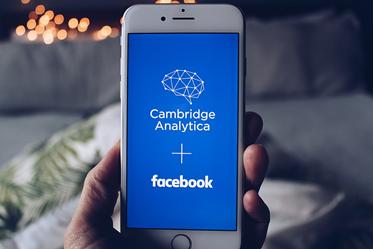 Foto von Smartphone auf dem die Logos von Cambridge Analytica und Facebook zu sehen sind.