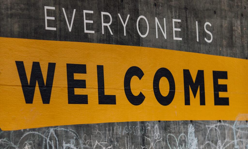 """Auf einer grauen Betonwand ist in Klebefolien-Buchstaben """"Everyone ist welcome!. Darunter Kreidekritzeleien."""