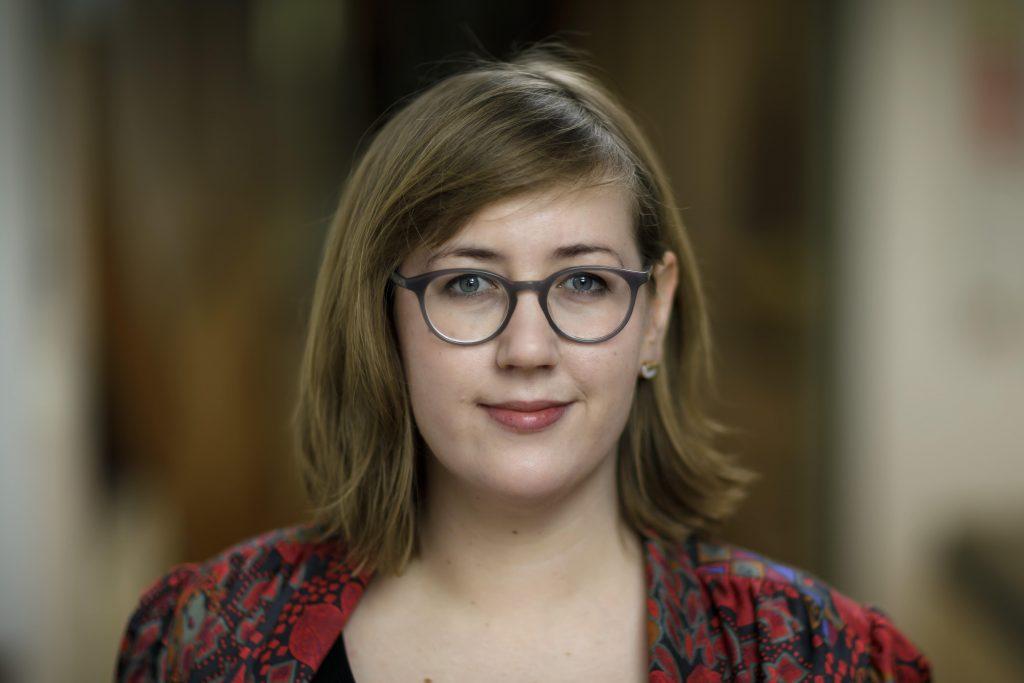 Judith Gehrke lachelt vor einem verschwommenen Hintergrund in die Kamera. Sie trägt eine Brille und kinnlange braune Haare.