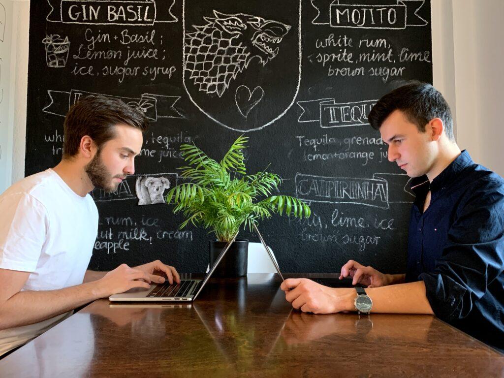Zwei junge Männer, Ole Friedrich und Julian von Lilienfeld sitzen in einem Café am Tisch, einander gegenüber mit Laptops - dahinter eine Tafel, auf der mit Kreide Cocktailrezepte geschrieben wurden.