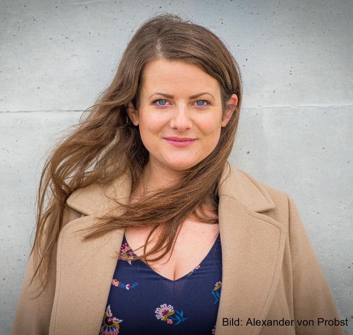 Foto von Ann-Cathrin Riedl mit offenen Haaren in die Kamera lächelnd vor einer Steinmauer frontal in die Kamera lächelnd.