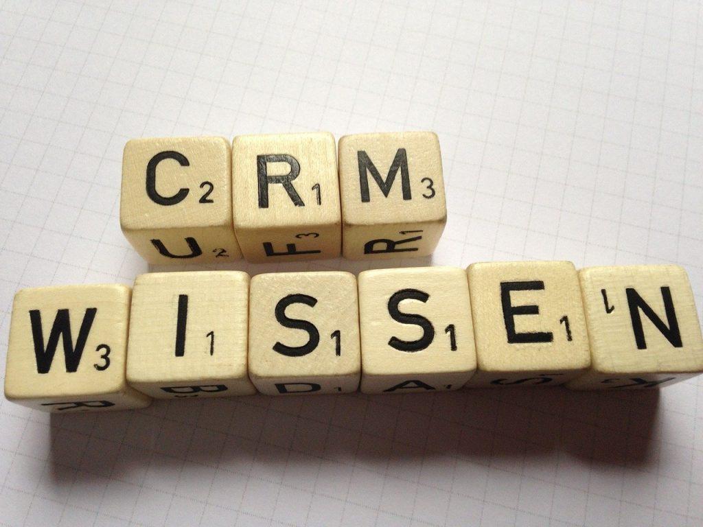 in zwei Reihen liegen Buchstabenwürfel auf einem Blatt Papier. Sie bilden die Worte CRM Wissen