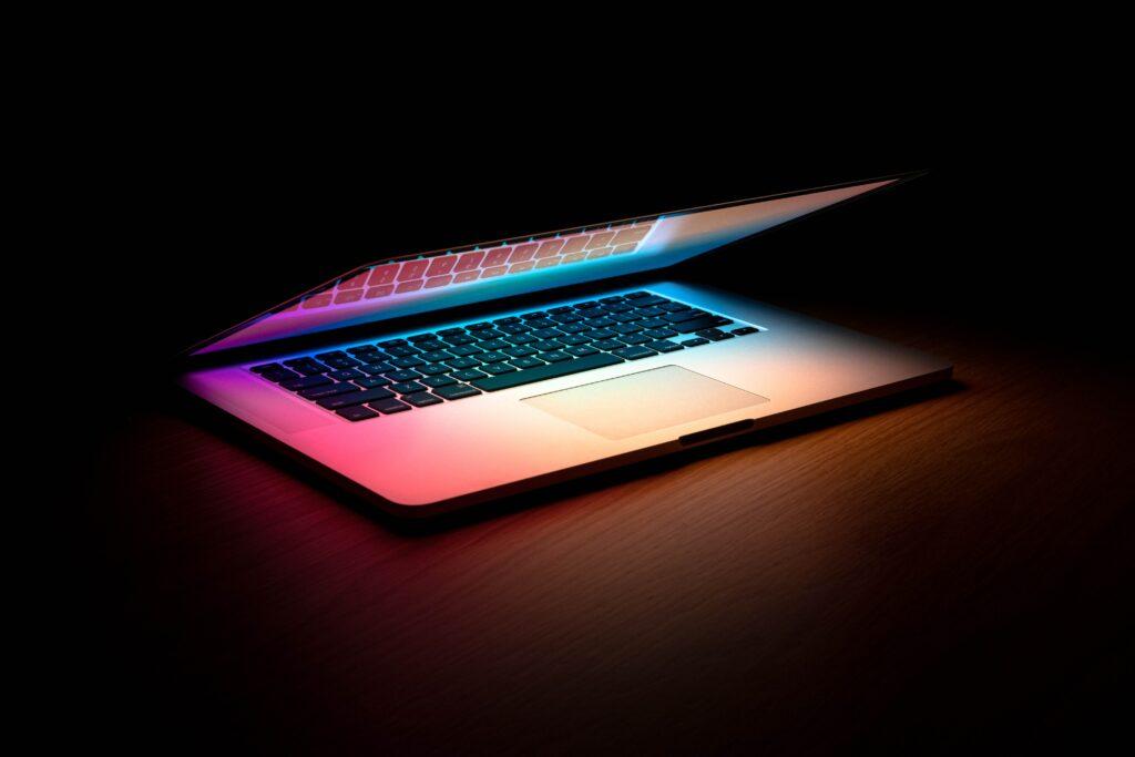 Ein Laptop steht halb zugeklappt im dunkeln, man sieht nur buntes Licht vom Bildschirm auf die Tastatur strahlen.