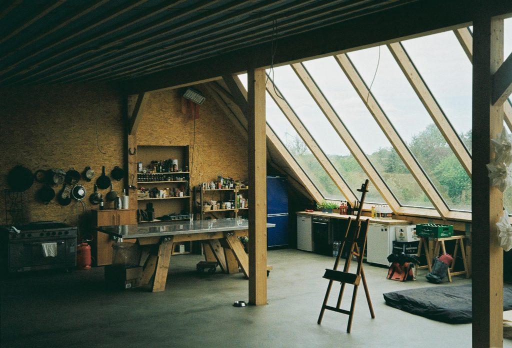 Blick in das Atelier 17111, einen hellen Dachboden, eine Dachseite besteht aus großen Dachfenstern bis zum Boden. Im Raum steht eine Küche, eine Staffelei, eine Matratze und eine Tischtennisplatte.