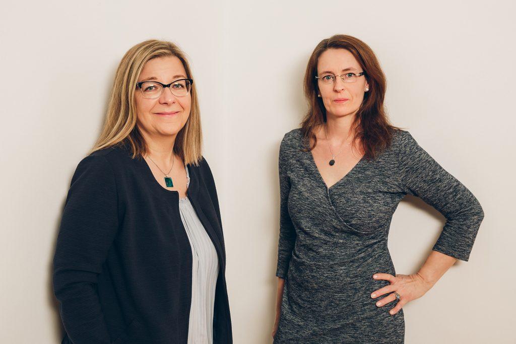 Daniela Schütt und Jana Stelzig stehen vor einer Wand und lächeln in die Kamera