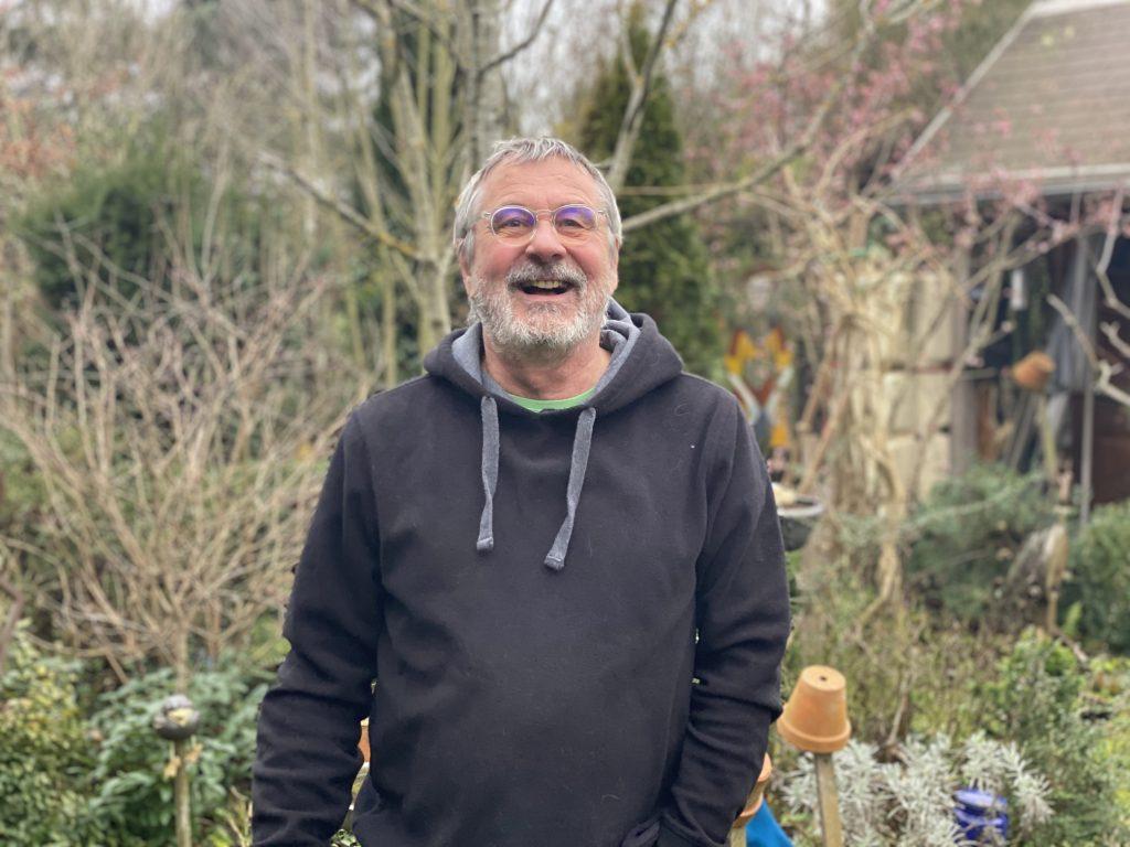Thomas Grünschläger von IFGL steht lachend in einem Garten