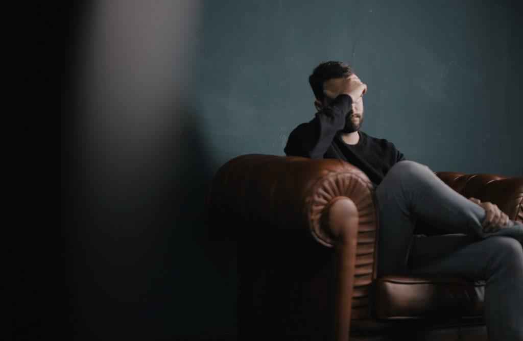 Ein Mann sitzt deprimiert, sich an den Kopf fassend auf einem Sessel, Foto durch die geöffnete Tür.