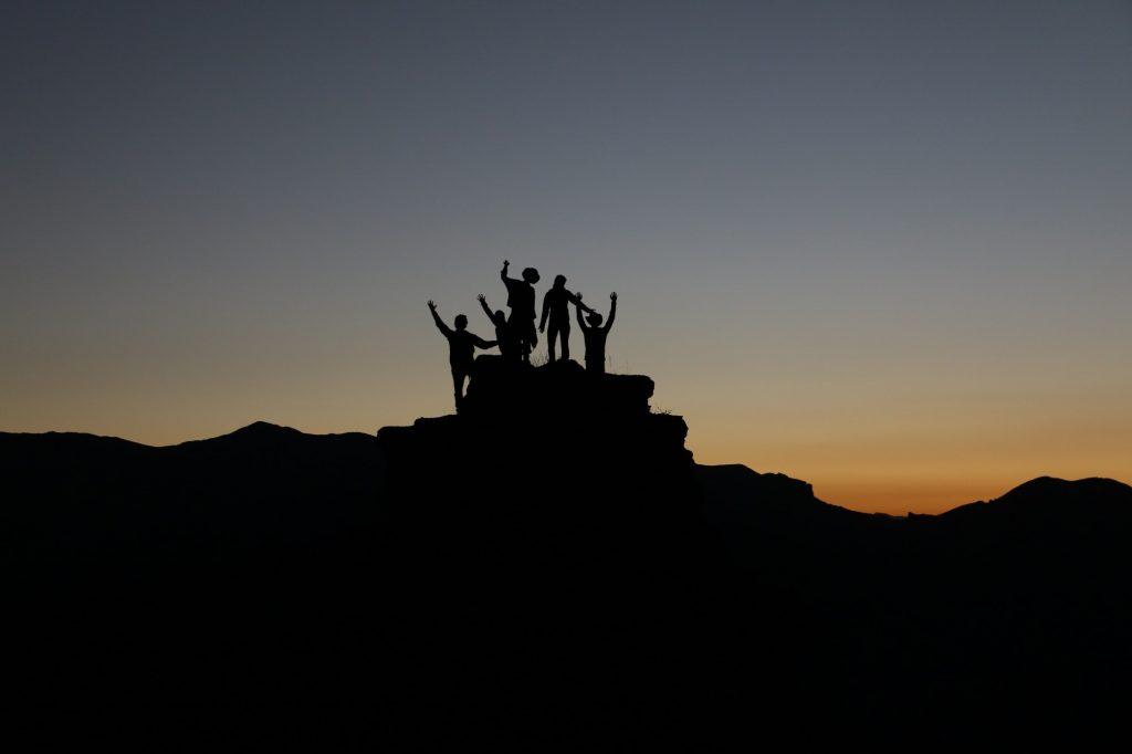 Foto von einer Gruppe von Menschen, die auf einer Hügelspitze stehen.
