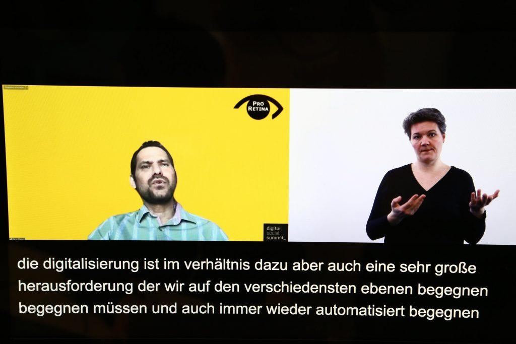 Foto auf dem Dario Madani sowie die Live-Gebärdendolmetscherin zu sehen ist: Digitale Barrierefreiheit.