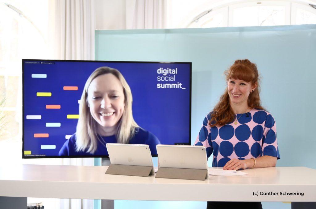 Foto vom Digital Social Summit 2021 und Moderatorin Theresa Sickert am Stehpult, Cathrin Heinrich ist auf dem Bildschirm im Hintergrund zu sehen..