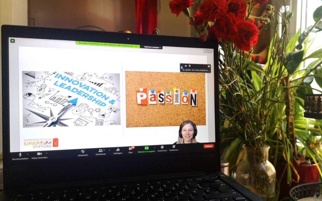 Nina Noenen bei ihrer Zoom-Präsentation auf dem Laptop, fotografiert vor einer Fensterbank voller Pflanzen.