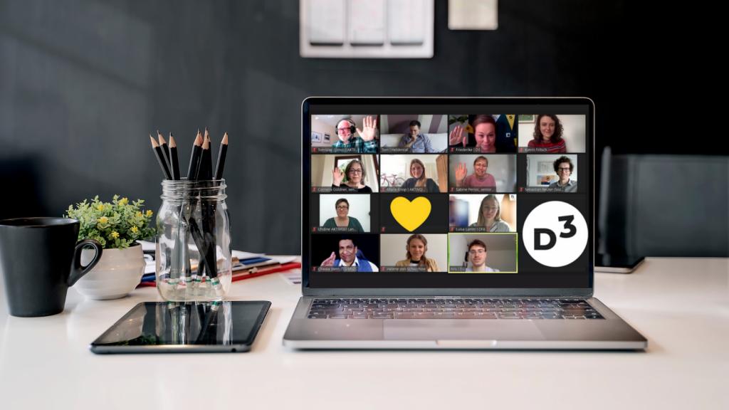 Auf einem Laptop sind die Teilnehmenden des D3 Meetups Digital Vereint zu sehen. Einige Kacheln sind mit Herzen und D3 Logo anonymisiert. Der Laptop steht auf einem modernen Schreibtisch vor taubenblauer Wand.