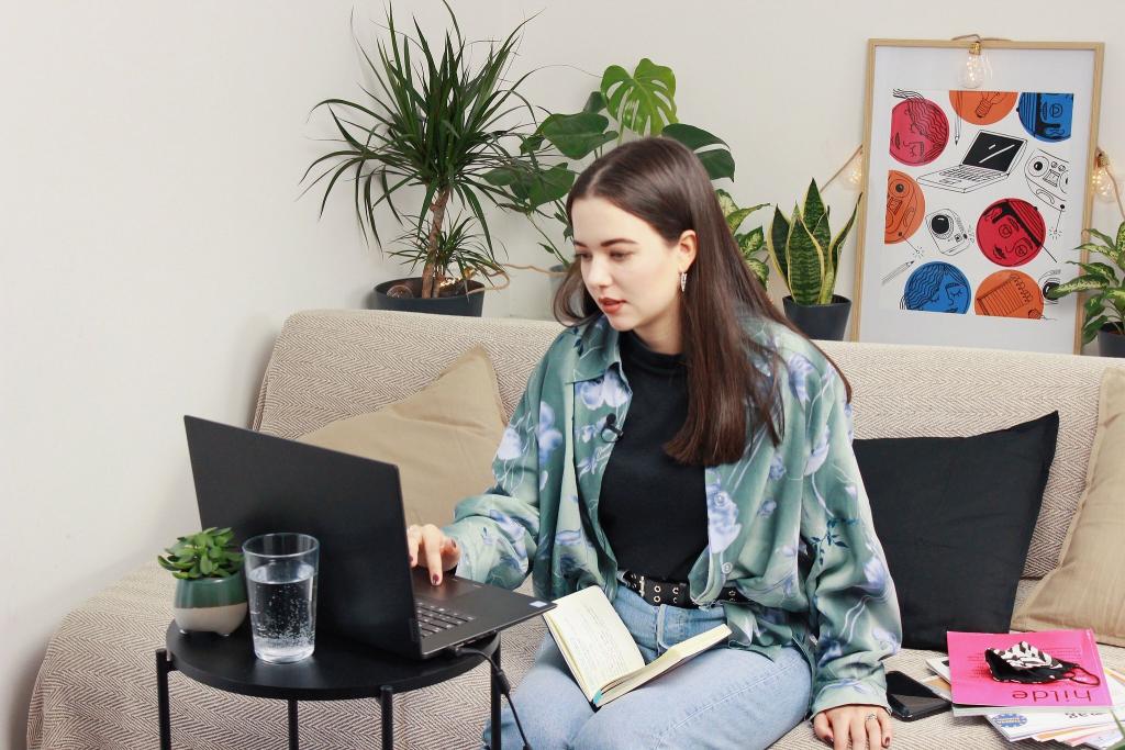 Eine Junge Frau sitzt auf einem Sofa und arbeitet am Laptop. Neben ihr liegen Schüler:innenmedien, um sie herum Grünpflanzen und bunte Bilder