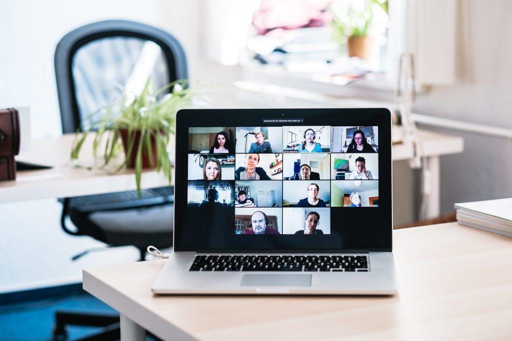 Foto eines Laptops, der auf einem Tisch steht und in dem eine Zoom-Konferenz stattfindet.