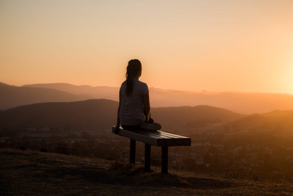 Frau meditiert im Sonnenaufgang auf einer Bank auf einem Berg, Blick ins Tal