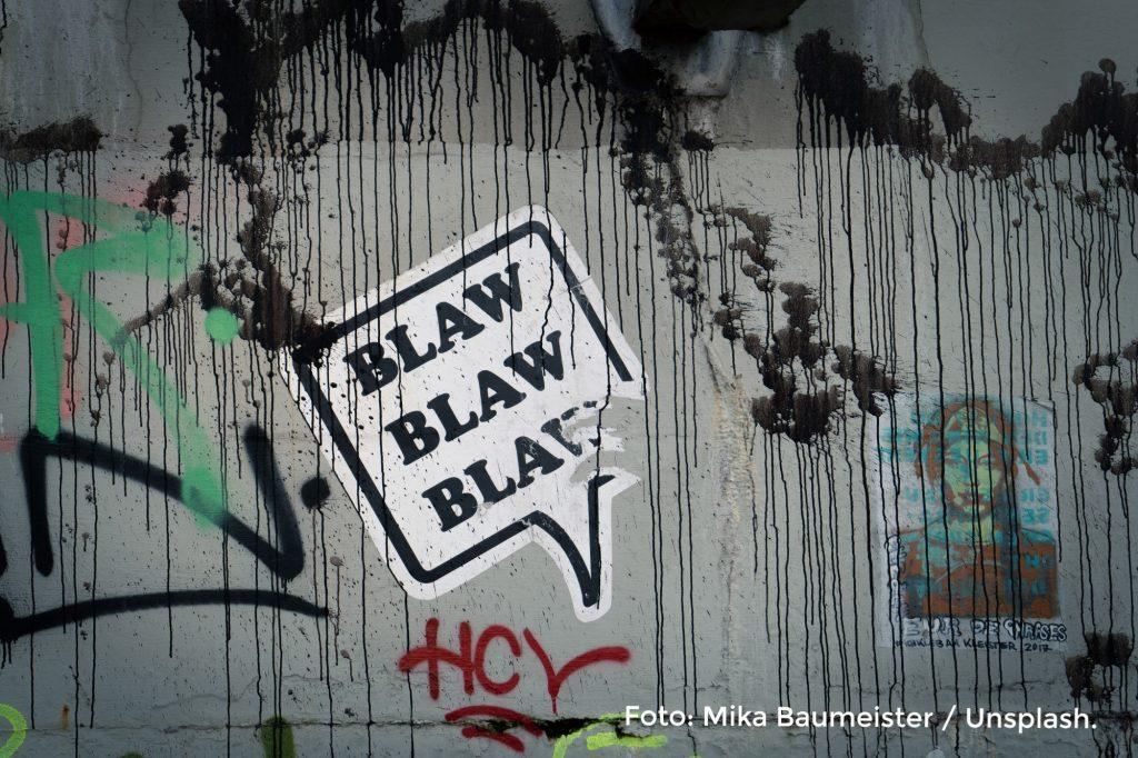 Symbolbild für Hate Speech im Internet. Foto einer Wand mit Graffiti, auf der ein Sprechblasensticker klebt.