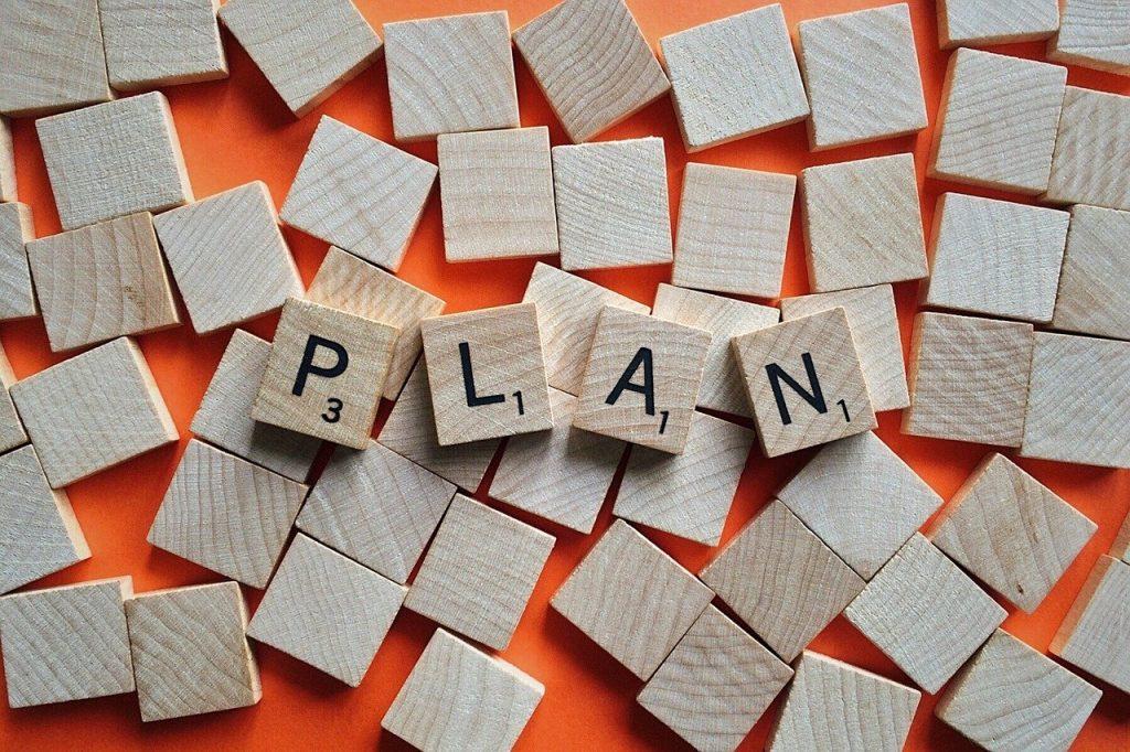 """Digital geht nur mit Plan. Auf einem Stapel blanko-Holzsteine liegen vier Holzsteine mit Buchstaben, die zusammen das Wort """"Plan"""" ergeben."""