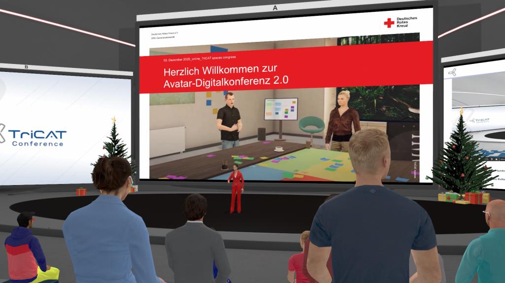"""Menschen-Avatare stehen in Rängen von hinten gescreenshottet vor einer virtuellen Bühne, auf der ein weiblicher Avatar die Begrüßung vor einer Präsentation mit den Worten """"Herzlich Willkommen zur Avatar-Digitalkonferenz 2.0"""" durchführt."""""""