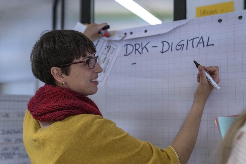 """Jennifer Geiser vom DRK steht bei einem Innovation-Workshop vor einem Flipchart und schreibt """"DRK-Digital"""" als Überschrift darauf."""