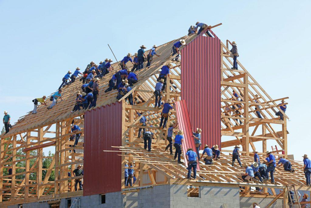 Dutzende Zimmermänner arbeiten Hand in Hand am Dachstuhl eines Gebäudeneubaus, ähnlich wie beim Online Fundraising viele Maßnahmen ineinandergreifen.