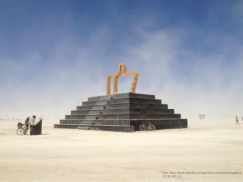 Ein Facebook-Likedaumen steht als große Statue wie die Pyramiden in einer Wüste.
