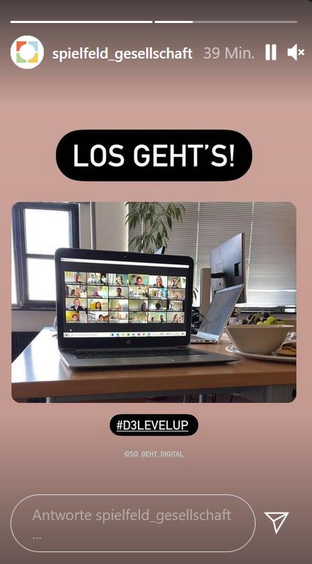 """Auf einem Tisch steht ein Laptop, der das Auftaktmeeting zu Level up! zeigt. Das Foto ist in eine Instagram-Story von Spielfeld Gesellschaft eingebettet. Darüber steht """"Los gehts!"""""""