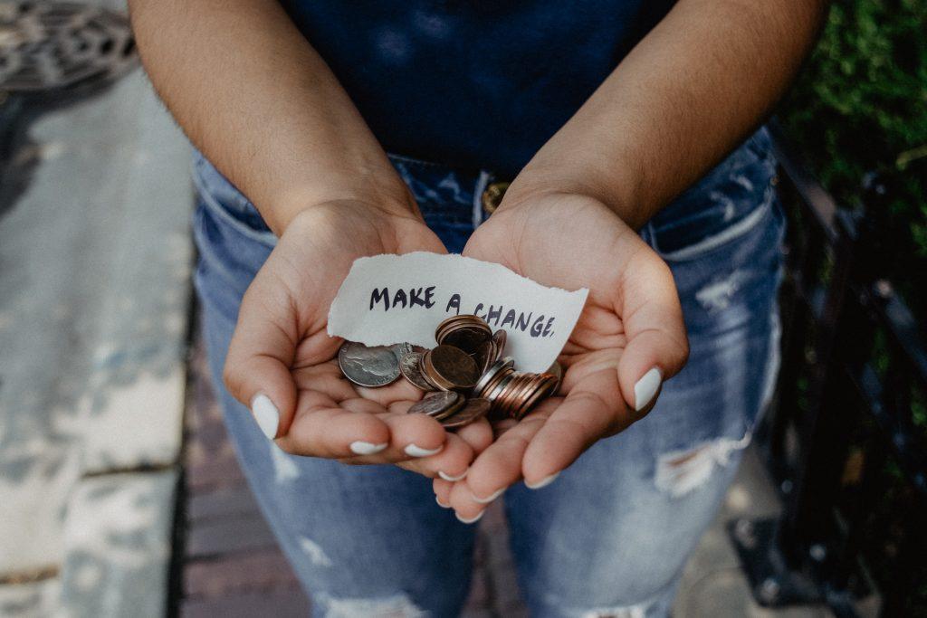 """Eine Person hält ihre offenen Hände in die Kamera, darin liegt Kleingeld und ein Zettel mit der Aufschrift """"Make a Change"""". Titelbild des Beitrags zu Spenden-Plattformen"""